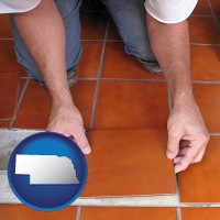nebraska map icon and a tile worker laying ceramic floor tile