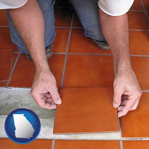 a tile worker laying ceramic floor tile - with Georgia icon