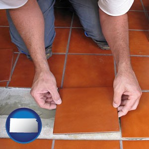 a tile worker laying ceramic floor tile - with Kansas icon