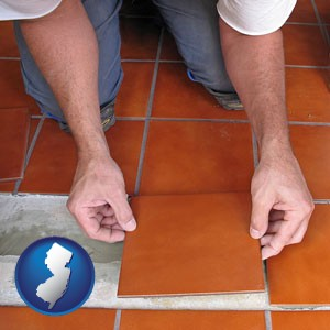 a tile worker laying ceramic floor tile - with New Jersey icon