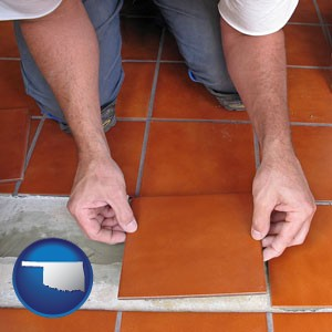 a tile worker laying ceramic floor tile - with Oklahoma icon