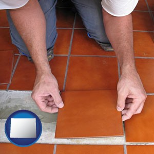 a tile worker laying ceramic floor tile - with Wyoming icon