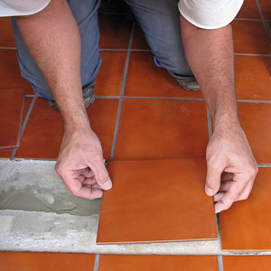 a tile worker laying ceramic floor tile